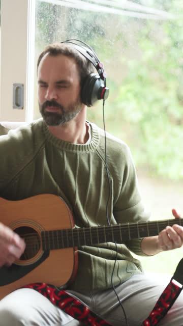vídeos y material grabado en eventos de stock de hombre tocando una guitarra acústica en su estudio casero - vídeo equipo eléctrico