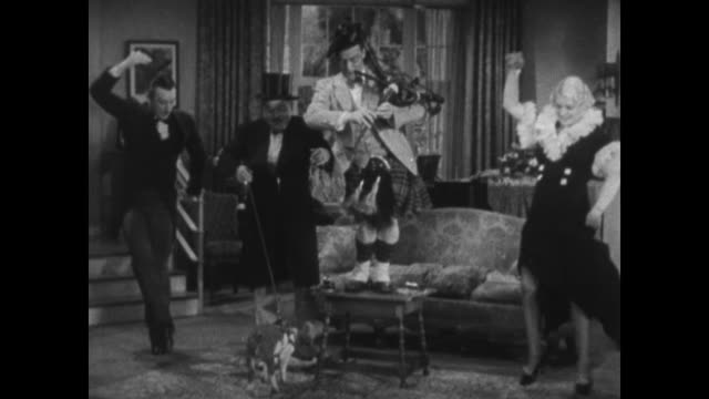 1934 Man playing bagpipe is followed by a man with pig on leash as they enter apartment and everyone starts dancing before introductions
