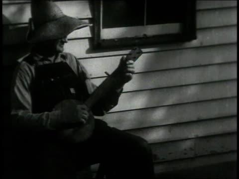 1946 montage man playing banjo / united states - banjo stock-videos und b-roll-filmmaterial