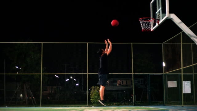 a man playing basketball on outdoor court by himself at night. - grandangolo tecnica fotografica video stock e b–roll