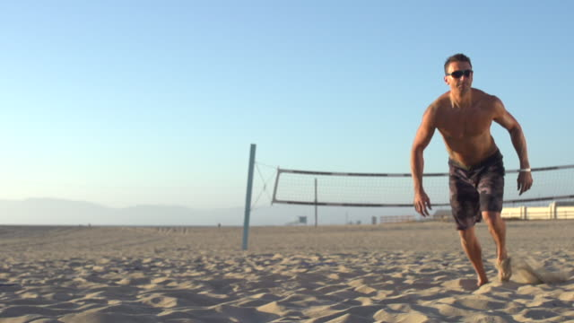 man playing beach volleyball. - slow motion - filmed at 240 fps - moving down stock videos & royalty-free footage