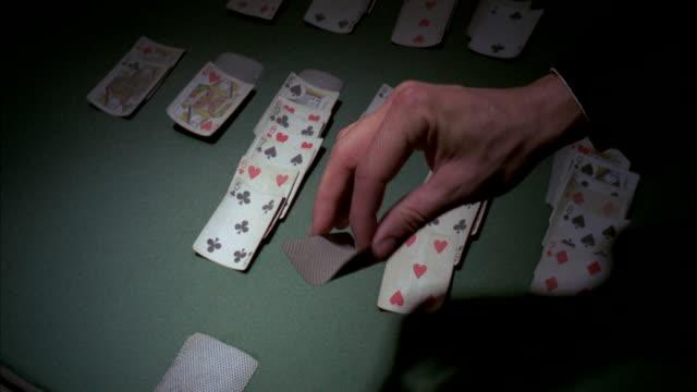 vidéos et rushes de cu tu man playing cards on table / los angeles, california, united states - jouer aux jeux de hasard