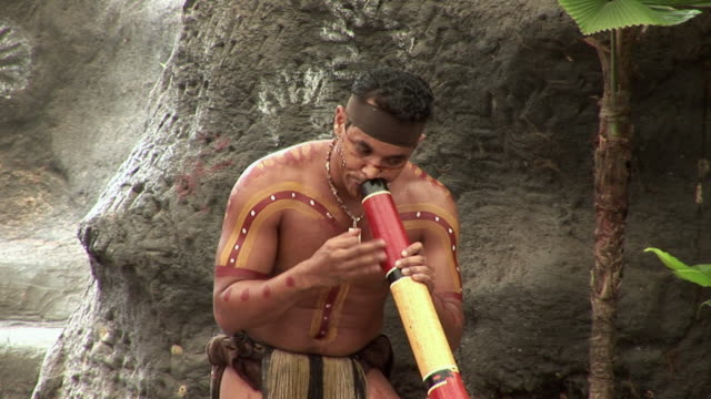 cu man playing didgeridoo sitting on floor on outdoor stage, queensland, australia - australian aboriginal culture stock videos and b-roll footage