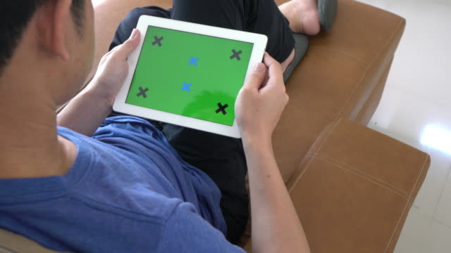 Man playing Digital Tablet With Green Screen