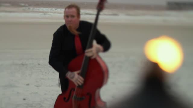 MS SELECTIVE FOCUS SHAKY Man playing double bass on beach / Jacksonville, Florida, USA