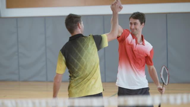 vídeos de stock, filmes e b-roll de homem jogando badminton indoor duplas fazendo um saque - badmínton esporte