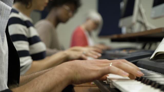 vídeos de stock e filmes b-roll de man playing electric keyboard in college music lesson. - só um homem de idade mediana