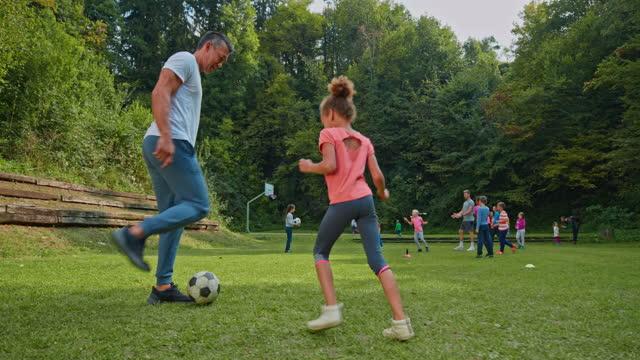 vídeos y material grabado en eventos de stock de hombre jugando al fútbol con su hija en la naturaleza - familia con un hijo