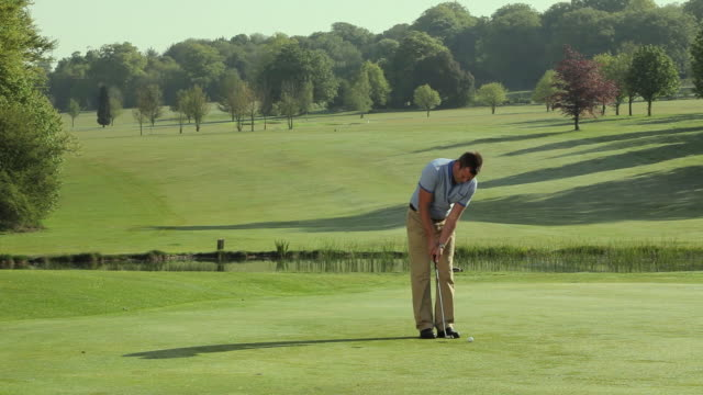 ws pan man playing golf / canterbury, kent, uk - putting stock videos and b-roll footage