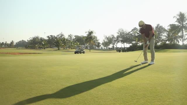 vídeos y material grabado en eventos de stock de man playing golf in a golf course  - putt