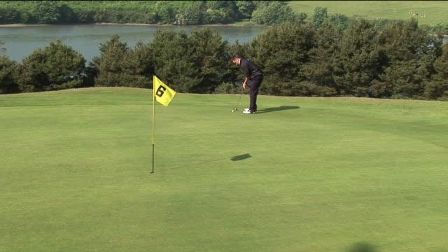 vidéos et rushes de ms, ha, man playing golf, kinsale, ireland - un seul homme d'âge moyen