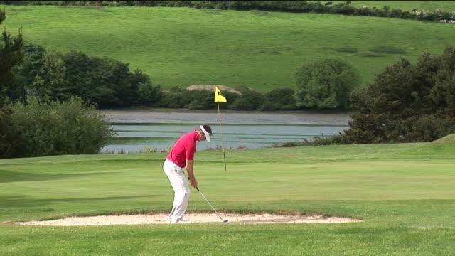 vídeos y material grabado en eventos de stock de ms, man playing golf, kinsale, ireland - bandera de golf
