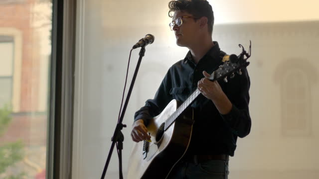 vidéos et rushes de man playing guitar in a small cafe with the sunset behind him. - anorexie nerveuse