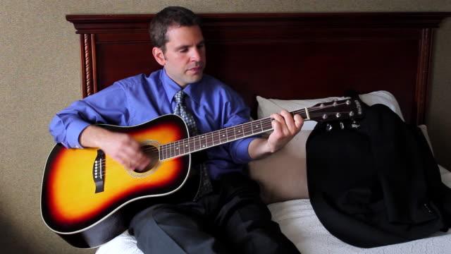 ms man playing guitar in hotel room / portland, me, united states - ホテルルーム点の映像素材/bロール