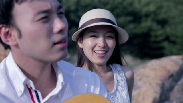 man playing guitar on a bench beside his girlfriend - korea点の映像素材/bロール