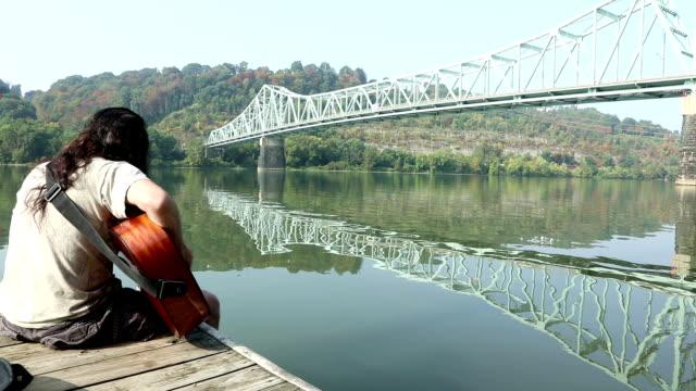 vidéos et rushes de homme, jouer de la guitare sur le quai de pont - rivière ohio