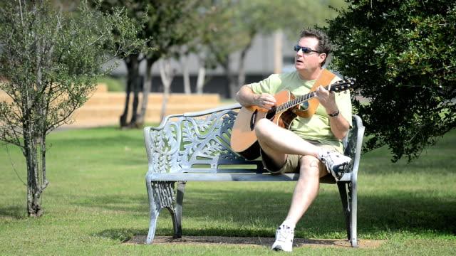 vídeos de stock e filmes b-roll de homem a tocar guitarra no banco de parque - só homens maduros