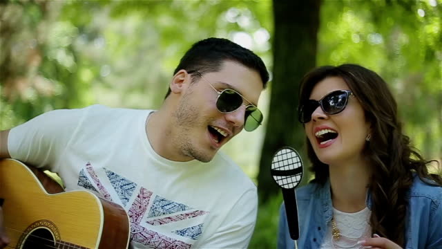 Man playing guitar to his girl on a picnic,close up