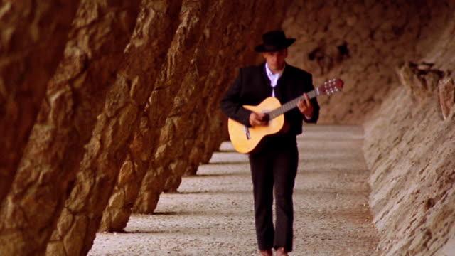 man playing guitar walking toward camera past slanted columns / parc guell, barcelona - traditional clothing stock videos & royalty-free footage