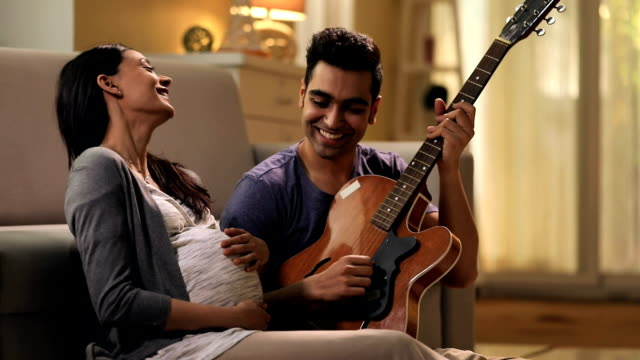 Man playing guitar with his pregnant wife, Delhi, India