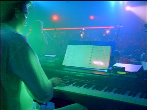 vídeos y material grabado en eventos de stock de rear view man playing keyboard on stage / bassist + singer in background - rock moderno