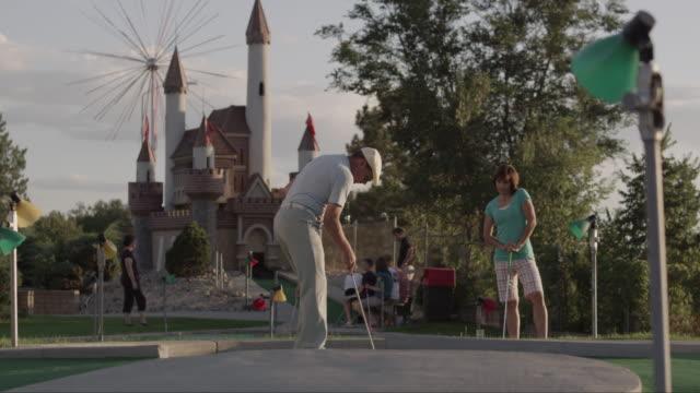 ws man playing mini golf, suddenly running around waving hands / orem, utah, usa - minigolf stock-videos und b-roll-filmmaterial