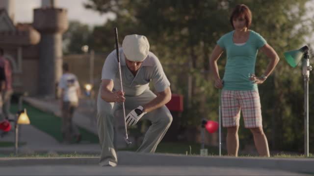 ms man playing mini golf, woman in background / orem, utah, usa - minigolf stock-videos und b-roll-filmmaterial