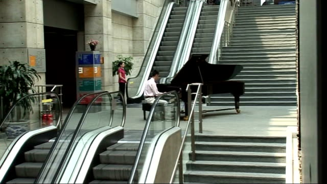 vidéos et rushes de man playing music at grand piano on floor between escalators sot people along on balcony various of lit-up models of city skyline in exhibition... - grand lit