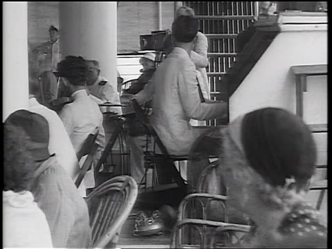 b/w 1934 man playing piano behind adults in wicker chairs watching offscreen children / cruise ship - 1934 stock videos & royalty-free footage