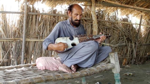 a man playing rubab (musical instrument) - 中年の男性だけ点の映像素材/bロール