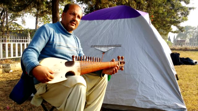 vidéos et rushes de a man playing rubab (musical instrument) while sitting outside the camp / tent - seulement des hommes d'âge mûr