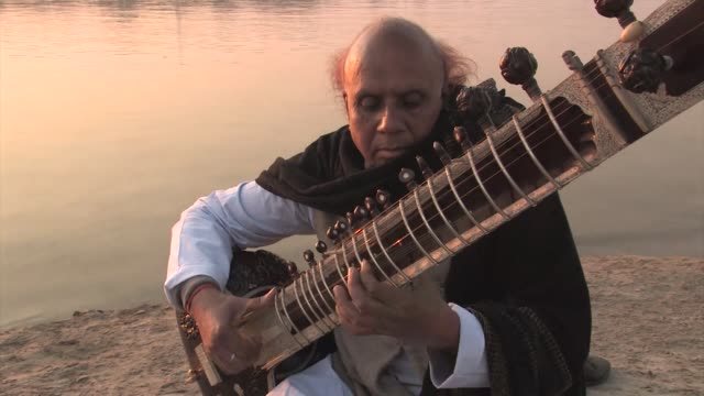 man playing sitar, sitting on a ghat next to the ganges river. editorial use only. - string instrument stock videos and b-roll footage