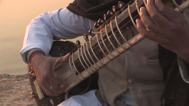 man playing sitar, sitting on a ghat next to the ganges river. editorial use only. - string instrument stock videos & royalty-free footage