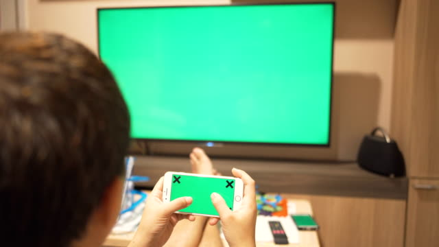 A man playing smartphone and watching TV,Green screen