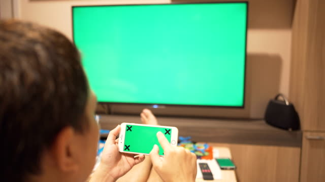 a man playing smartphone and watching tv,green screen - television game show stock videos & royalty-free footage