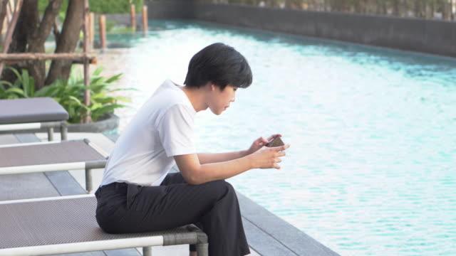 en man som spelar smartphone vid poolen - utebassäng bildbanksvideor och videomaterial från bakom kulisserna