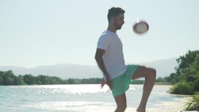 vídeos y material grabado en eventos de stock de man playing soccer football on a jetty on summertime. young adult juggling a ball. for the love of the game: soccer/futbol - patadas