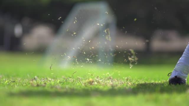 a man playing soccer on a grassy field. - slow motion - filmed at 240 fps - 蹴る点の映像素材/bロール