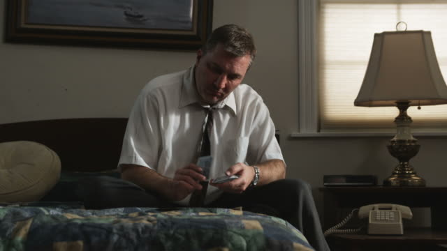 man playing solitaire in his motel room - solo un uomo video stock e b–roll