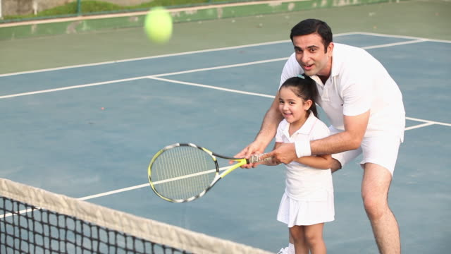 man playing tennis with his daughter  - mädchen stock-videos und b-roll-filmmaterial