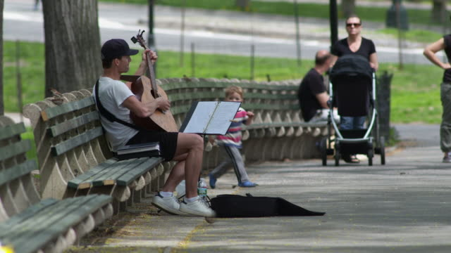 a man playing the guitar on a park bench in central park.  two little children come over to watch. - ベンチ点の映像素材/bロール