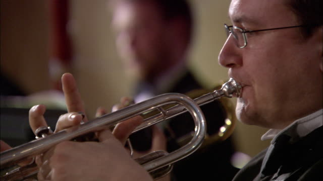 cu man playing trumpet in orchestra, musicians in background / london, united kingdom - brass instrument stock videos & royalty-free footage