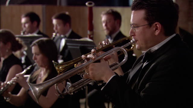 ms man playing trumpet in orchestra, musicians in background / london, united kingdom - orchestra stock videos & royalty-free footage
