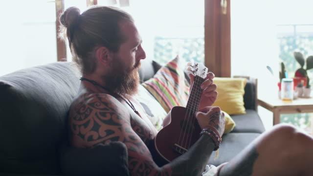 vídeos de stock e filmes b-roll de man playing ukulele - só um homem de idade mediana