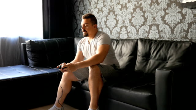 man playing video games on the couch - gamepad stock videos & royalty-free footage