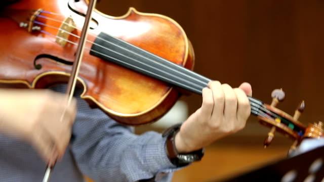 Man playing violin indoors.