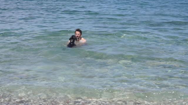 vidéos et rushes de homme qui joue avec son chien sur la plage - propriétaire d'animal de compagnie