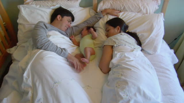 OH MS Man playing with newborn baby daughter as he lies in bed with wife sleeping on the other side/ San Antonio, Texas