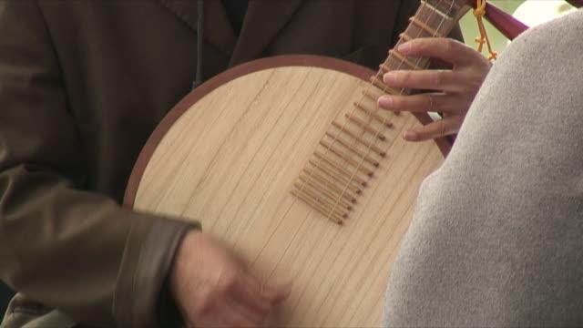 vídeos de stock, filmes e b-roll de cu tu man playing yueqin, kunming, china - dedilhando instrumento
