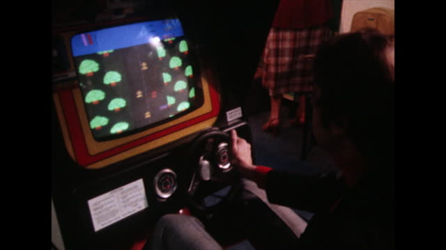 man plays a driving arcade game in 1980 - computer graphic stock videos & royalty-free footage